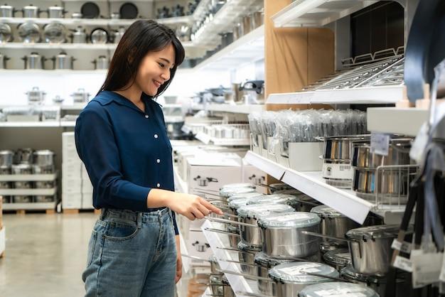 Asiatische frauen entscheiden sich dafür, neues küchengeschirr im einkaufszentrum zu kaufen. einkaufen für lebensmittel und haushaltswaren.