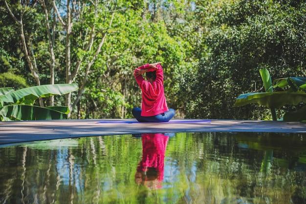 Asiatische frauen entspannen sich im urlaub. spielen sie yoga am pool. reisenatur der jungen frau sie stehende übung.