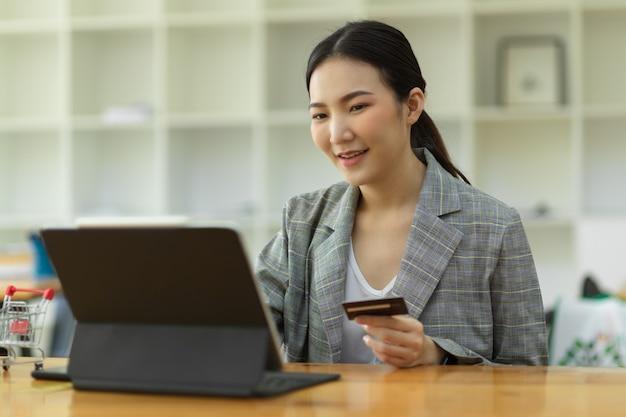 Asiatische frauen halten kreditkarte mit digitalem tablet, um die kartennummer beim internet-banking zu überprüfen