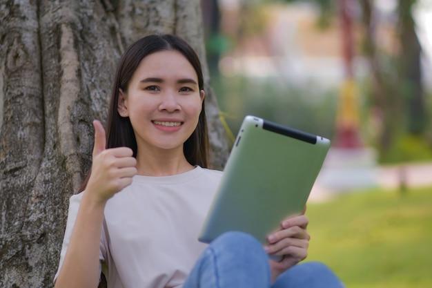 Asiatische frauen halten tablette auf sozialem netzwerk und kaufen online durch internet, das im stadtpark sitzt
