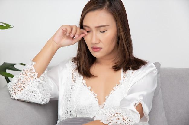 Asiatische frauen in der weißen satin-nachtwäsche kratzen sich aufgrund einer allergie in einem raum die augenlider