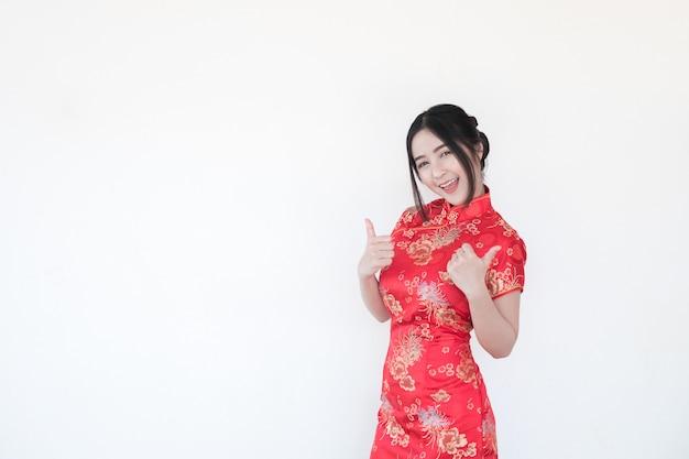 Asiatische frauen in traditionellem chinesischem cheongsam mit einer geste der glückwünsche.