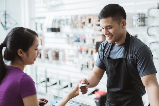 Asiatische frauen kaufen in einem fahrradausrüstungsgeschäft. mit kreditkarte