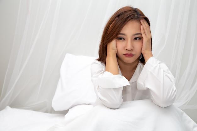 Asiatische frauen mit gefühlen der hilflosigkeit und hoffnungslosigkeit auf weißem bett im schlafzimmer, entweder schlaflosigkeit, depressionssymptome und warnzeichenkonzept