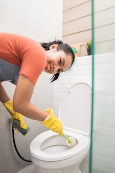 Asiatische frauen mit handschuhen reinigen die toilette im badezimmer mit einer bürste und einem porzellanreiniger