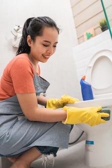 Asiatische frauen mit handschuhen reinigen die toilette mit einem schwamm im badezimmer