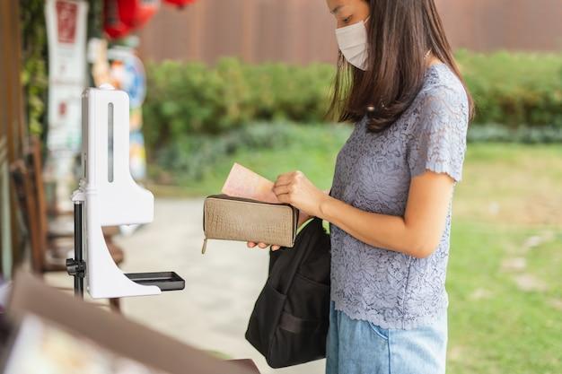 Asiatische frauen mit medizinischer maske nehmen banknoten aus ihrer handtasche.