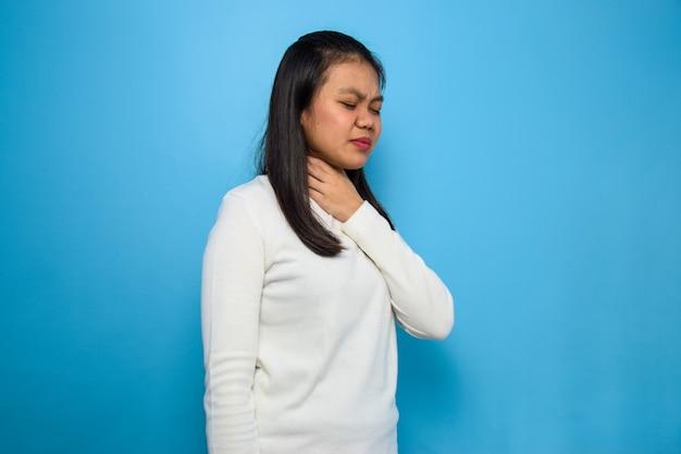 Asiatische frauen mit weißem t-shirt mit blauem isoliertem hintergrund frauen halsschmerzen covid19