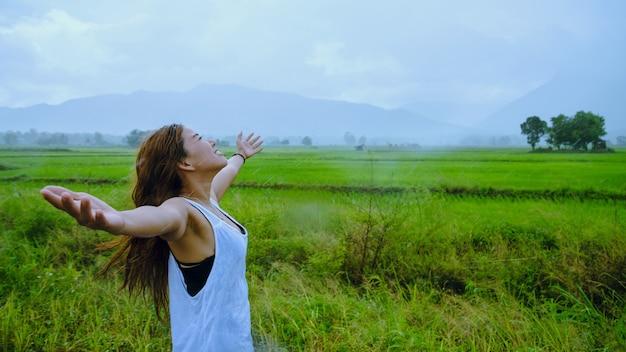 Asiatische frauen reisen im urlaub entspannen. das mädchen lächelte glücklich und genoss den regen, der fiel. reisen in länder, grüne reisfelder, reisen thailand.