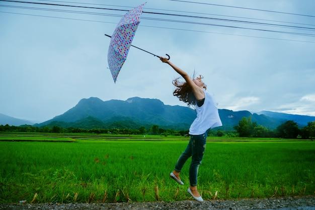 Asiatische frauen reisen im urlaub entspannen. die frauen standen glücklich einen regenschirm im regen und genießen den regen, der fällt. reisen in länder, grüne reisfelder, reisen thailand.