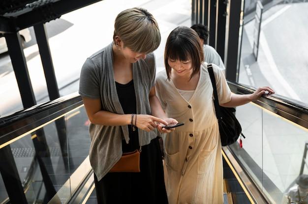 Asiatische frauen schauen sich etwas am telefon an