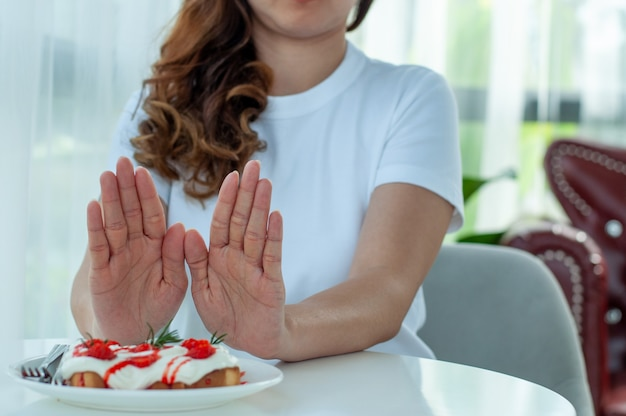 Asiatische frauen schieben den dessertteller mit beiden händen. abnehmende lebensmittel, die süß sind. richtlinien zum abnehmen. entscheiden sie, was gut für den körper ist.