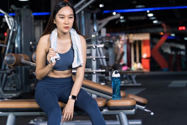 Asiatische frauen sitzen auf der übung und halten handtücher mit wasserflaschen auf den seiten