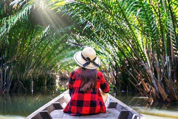 Asiatische frauen sitzen auf einem boot im tunnel von nypa fruticans oder palme in surat thani, thailand.