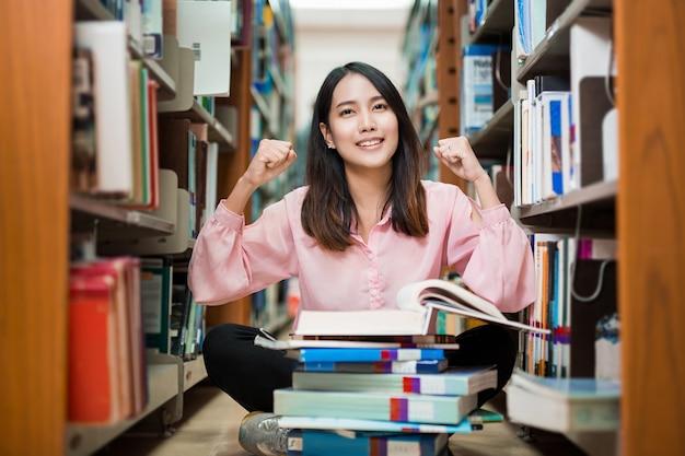 Asiatische frauen sitzen in der bibliothek a benommen