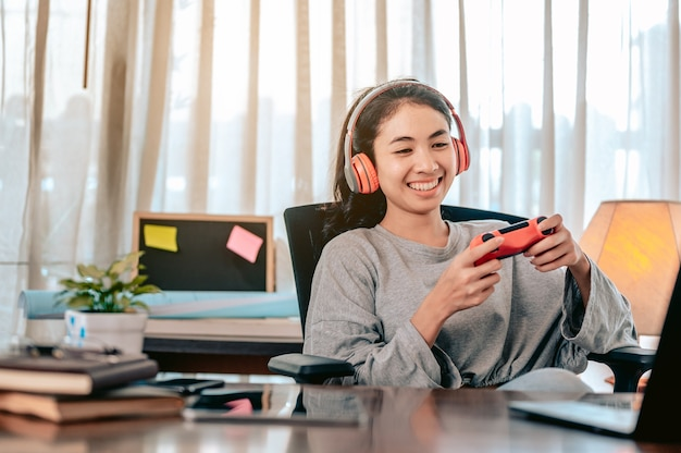 Asiatische frauen spielen im wohnzimmer zu hause im urlaub von der arbeit entspannende spiele