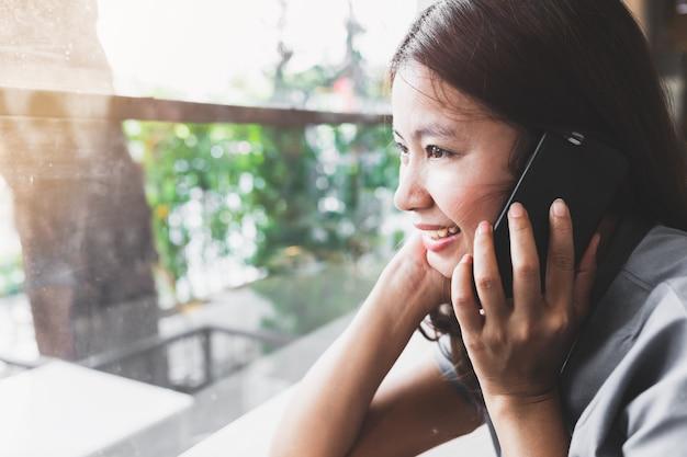 Asiatische frauen sprechen gerne mit mobiltelefonen in cafés