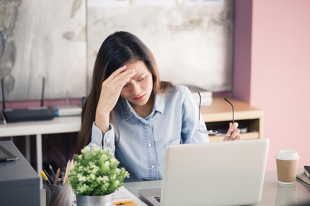 Asiatische frauen stressig mit einem notebook für eine lange zeit arbeiten, office-syndrom-konzept