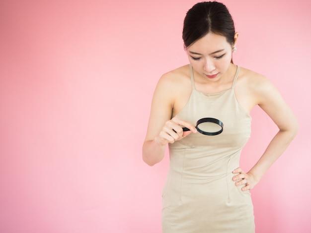 Asiatische frauen suchen durch eine lupe nach etwas und berühren ihren mund