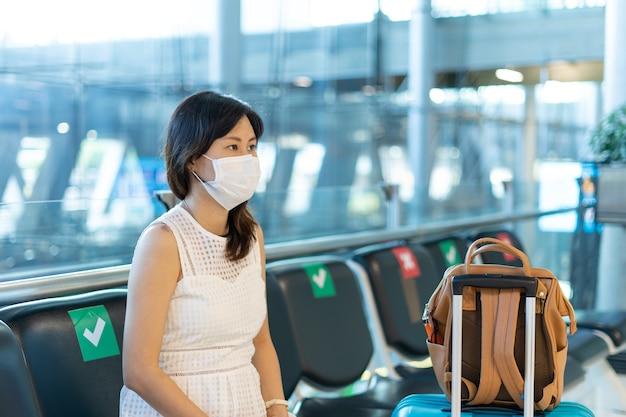 Asiatische frauen tragen eine maske und sitzen zwischen stühlen, um die ausbreitung des coronavirus zu reduzieren. touristen warten während des ausbruchs von covid-19 darauf, in flugzeuge zu steigen.