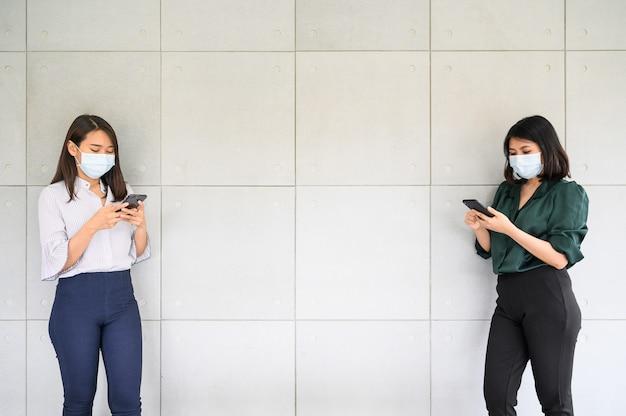 Asiatische frauen tragen gesichtsmaske mit smartphone und halten soziale distanz