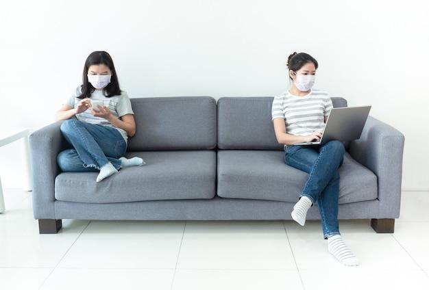 Asiatische frauen tragen masken, die zu hause mit notebook und smartphone arbeiten, um die ausbreitung der coronavirus-infektion während der krise von covid-19 zu verringern. arbeit von zu hause aus und soziales distanzierungskonzept.