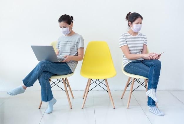 Asiatische frauen tragen masken, die zu hause mit notebook und smartphone arbeiten, um die ausbreitung der coronavirus-infektion während des covid-19-ausbruchs zu verringern.