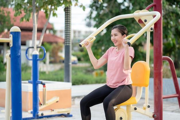 Asiatische frauen trainieren im park, nutzen die geräte, um sich zu bewegen und fit, gesund und in guter form zu bleiben.