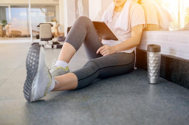 Asiatische frauen trainieren und arbeiten allein online im gym. soziale distanzierung und neuer normaler lebensstil.