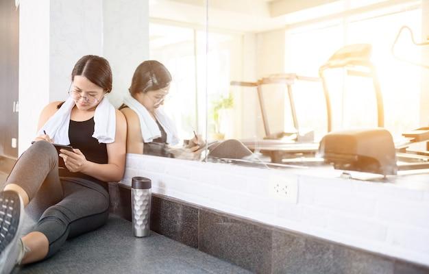 Asiatische frauen trainieren und arbeiten allein online im gym.