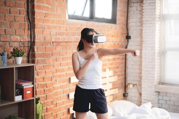 Asiatische frauen trainieren zuhause drinnen sie benutzt vr-brillen beim boxen.