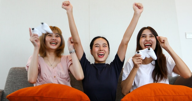 Asiatische frauen und freunde spielen zu hause und lachen aufgeregt auf dem sofa zu hause.
