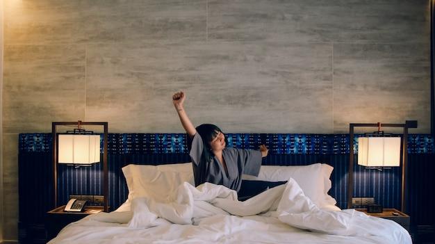 Asiatische frauen wachen aus dem schlaf auf strecken sich am morgen am wochenende auf dem bett im luxuszimmer im relax- und wochenend-konzept