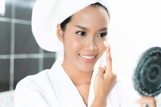 Asiatische frauen wenden creme und lotion auf ihr gesicht an, nachdem sie im badezimmer gebadet haben.