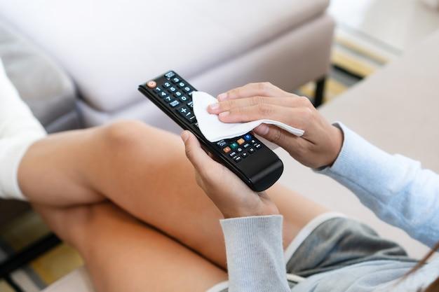 Asiatische frauenhände, die die tv-fernbedienung mit desinfizierenden feuchttüchern reinigen