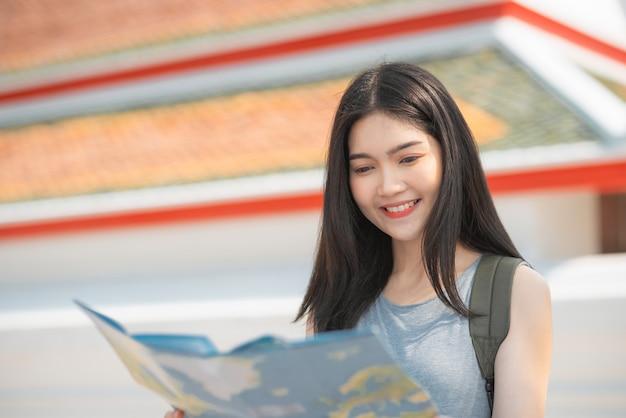 Asiatische frauenrichtung des reisenden auf standortkarte in bangkok, thailand