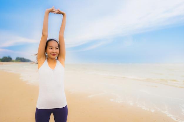 Asiatische frauenübung des schönen jungen sports des porträts durch laufen und rütteln auf dem naturstrand und -meer im freien