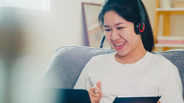Asiatische freiberufliche geschäftsfrau freizeitkleidung unter verwendung von laptop-arbeitsanruf-videokonferenz mit kunden am arbeitsplatz im wohnzimmer von zu hause aus, wenn soziale distanzierung zu hause bleibt und selbstquarantänezeit.