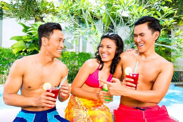 Asiatische freunde, die cocktails am pool trinken