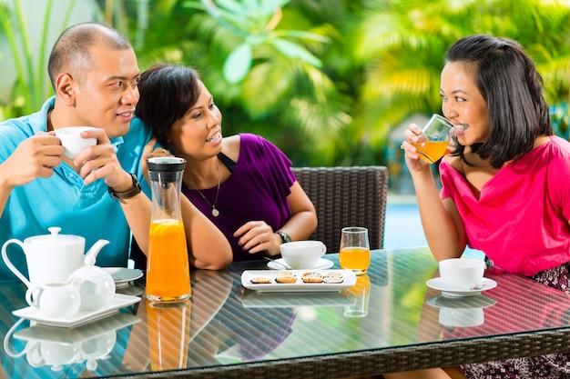 Asiatische freunde, die kaffee auf hauptportal trinken