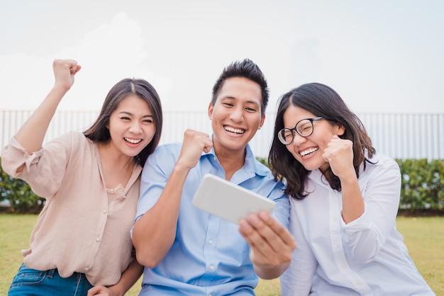 Asiatische freunde, die smartphone aufpassen und spaß haben