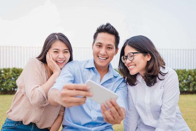 Asiatische freunde, die spaß haben, sachen auf smartphone aufzupassen