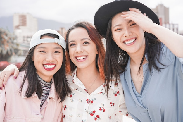 Asiatische freundinnen, die spaß im freien haben. glückliche trendige mädchen, die zusammen lachen