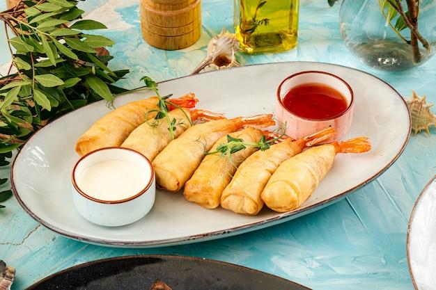 Asiatische frittierte frühlingsrollen mit garnelen mit saucen