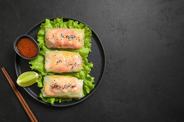 Asiatische frühlingsrollen mit garnelen, die in reispapier auf schwarzem steinhintergrund eingewickelt werden. von oben betrachten. asiatische küche.