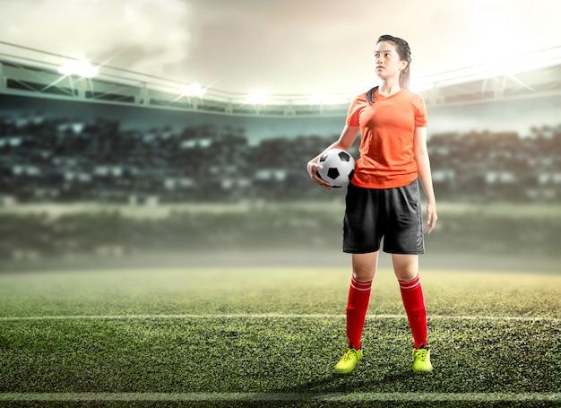 Asiatische fußballspielerfrau, die den ball auf dem fußballplatz hält