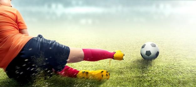 Asiatische fußballspielerfrau im orange trikot, das gerät die kugel schiebt
