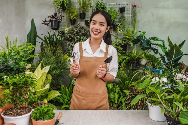 Asiatische gärtnerin, die einen schürzenständer trägt und eine schaufel und eine heugabel zeigt, ausrüstung zum transplantieren von zimmerpflanzen und zur pflege von pflanzen zu hause