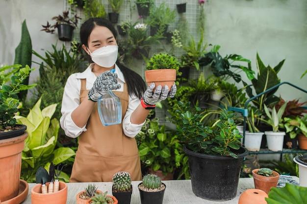 Asiatische gärtnerin mit gesichtsmaske und schürze, die spray hält, um grüne zimmerpflanze in der hand zu gießen