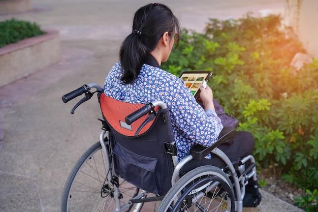 Asiatische geduldige gebrauchstablette der damenfrau von mittlerem alter auf rollstuhl im park.